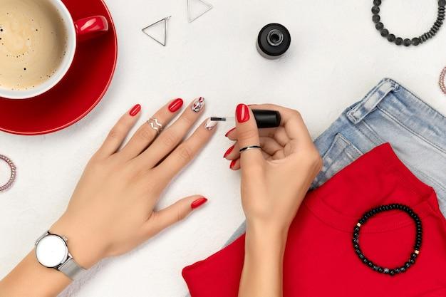 Womans ręka z czerwonym manicure, trzymając butelkę lakieru do paznokci