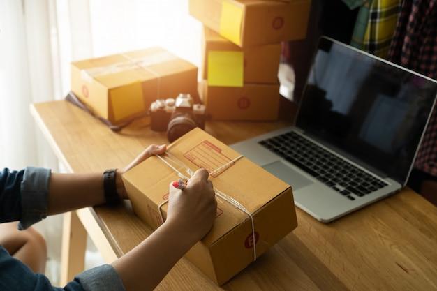 Womans ręka z pakowaniem kartonu w miejscu pracy, sprzedaż online