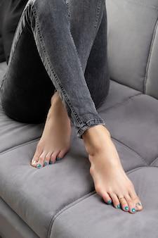 Womans stóp w dżinsach z pedicure na szarej kanapie w domu