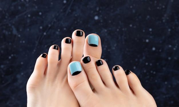 Womans stopy na ciemnym tle. piękny wiosenno-letni niebieski i czarny wzór paznokci. manicure, koncepcja gabinetu kosmetycznego pedicure.