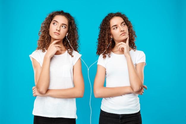 Womans twins słucha muzyki w słuchawkach, myśląc nad niebieskim.