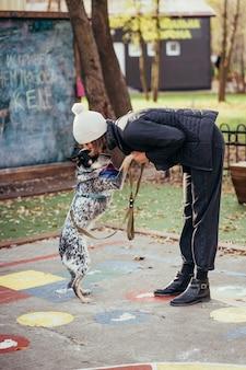 Wonam i pies kundel na spacer w jesiennym parku