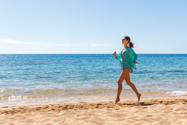 Wooman biegnie po plaży w słoneczny dzień. letnia dziewczyna plażowa