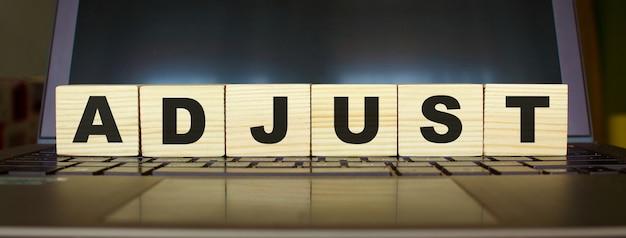 Word adjust. drewniane kostki z literami na białym tle na klawiaturze laptopa. obraz koncepcji biznesowej.