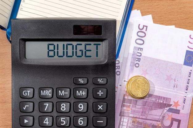 Word budżet na wyświetlaczu kalkulatora na biurowym stole z banknotami euro. pomysł na biznes