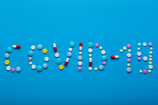 Word covid 19 napisał wielokolorowymi pigułkami na niebieskim tle z wolnym miejscem na tekst