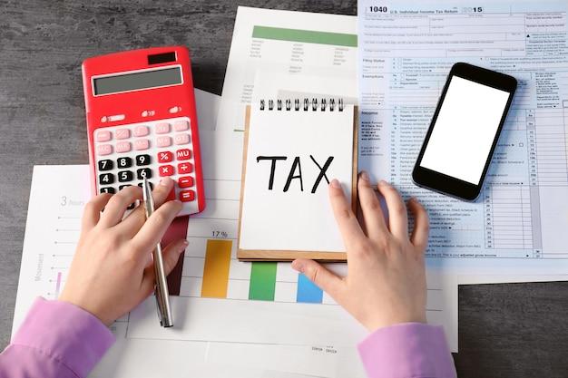 Word tax na kartce papieru i kobiece dłonie pracujące z dokumentami przy stole