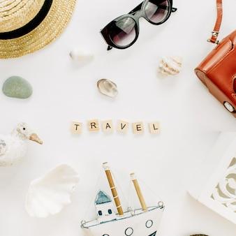 Word travel, figurka ptaka, zabawkowa łódka, aparat retro, muszle i słomkowy kapelusz na białej powierzchni