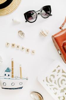 Word travel, zabawkowa łódka, retro aparat, muszle i słomkowy kapelusz na białej powierzchni
