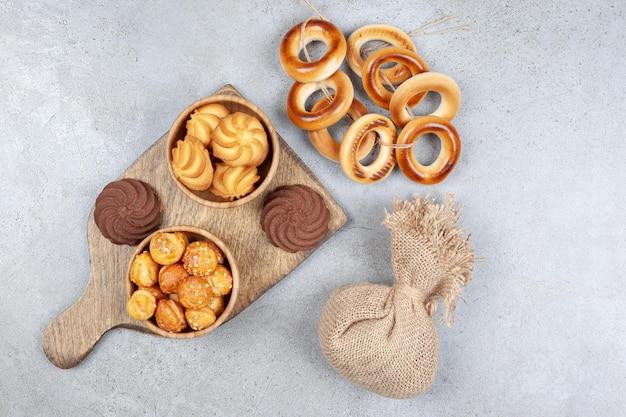 Worek i zawiązany pierścień sushki obok miseczek z ciasteczkami obok brązowych ciasteczek na drewnianej desce na marmurowym tle. wysokiej jakości zdjęcie
