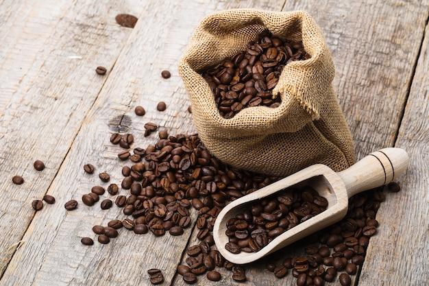 Worek kawy na starym drewnianym stole i worek ziaren kawy
