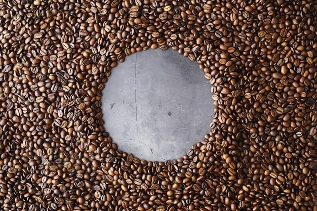 Worek kawy. ziarna kawy prażone na stole. ziarna kawy z zielonymi liśćmi do gotowania.