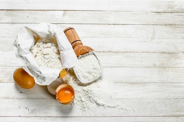 Worek mąki i jajek. na białym drewnianym stole.