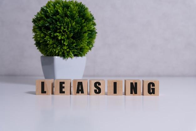 Worek na pieniądze i klocki z napisem leasing. leasing to ustalenia umowne wymagające od leasingobiorcy zapłaty leasingodawcy za użytkowanie składnika aktywów. nieruchomości, pojazdy to wspólne aktywa, które są przedmiotem leasingu.