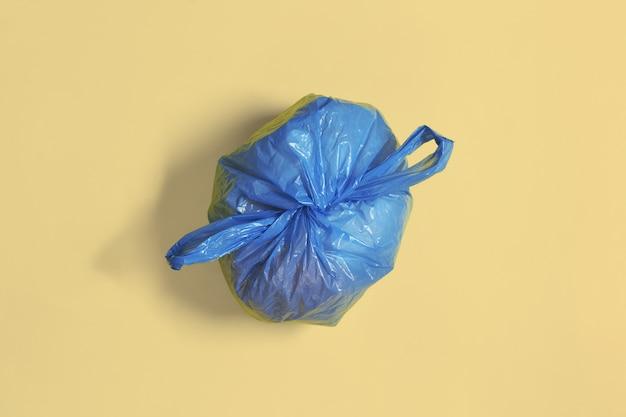 Worek na śmieci zawiązany węzłem na delikatnym kolorowym tle