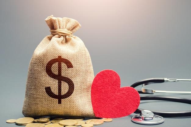 Worek pieniędzy dolara i stetoskop. ubezpieczenie zdrowotne na życie i koncepcja finansowania.