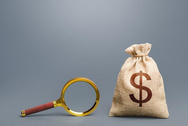 Worek pieniędzy dolara i szkło powiększające. audyt finansowy. pochodzenie kapitału i legalność funduszy