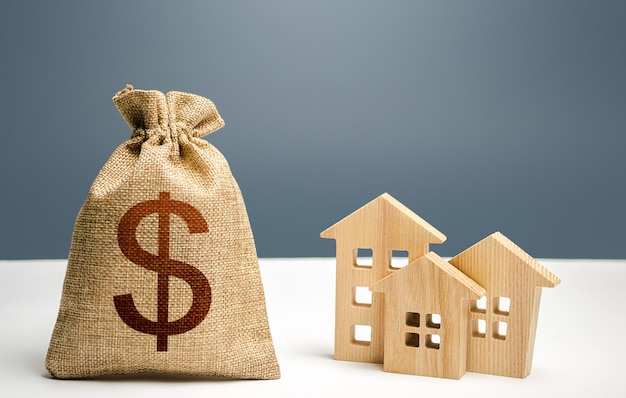 Worek pieniędzy i figurki budynków mieszkalnych. kredyt hipoteczny. miejski budżet miejski