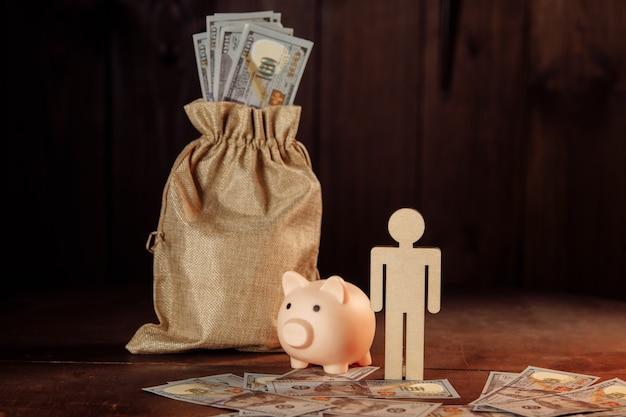Worek pieniędzy skarbonka i postać człowieka. koncepcja inwestycji i oszczędności