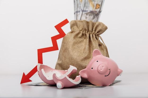 Worek pieniędzy, złamana skarbonka i czerwona strzałka w dół. stagnacja, recesja, malejąca aktywność biznesowa, malejący majątek.