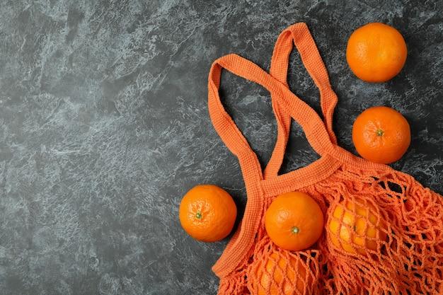 Worek sznurkowy z mandarynkami na czarnym tle smokey