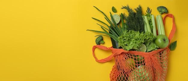 Worek sznurkowy z zielonymi warzywami na żółtym tle