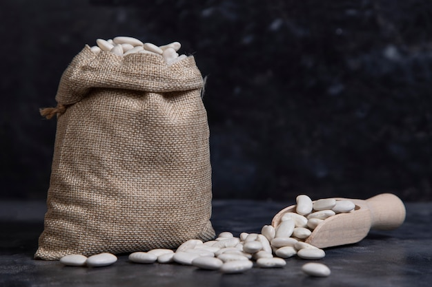 Worek wypełniony suchymi fasolkami maślanymi ułożonymi na kamieniu