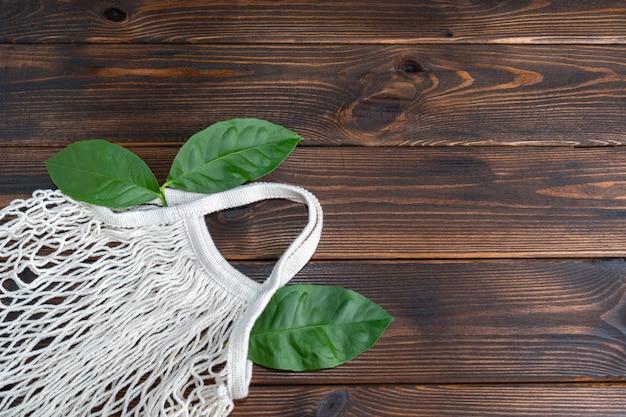 Worek z siatki wielokrotnego użytku leży na drewnianym tle. koncepcja zero odpadów. skopiuj miejsce. widok z góry.