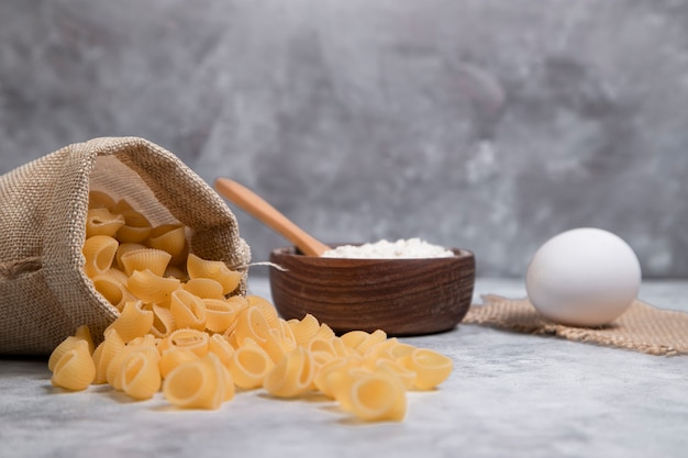 Worek z suszonego makaronu w kształcie muszli z drewnianą miską mąki