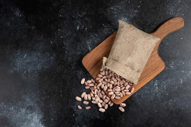 Worek z suszonej surowej fasoli umieszczony na desce.