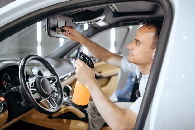 Worker sprayem nawilża wnętrze samochodu, czyści chemicznie i detalicznie
