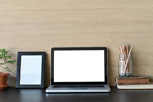 Workspace makieta laptop i materiały biurowe na biurku i drewnianej ścianie.