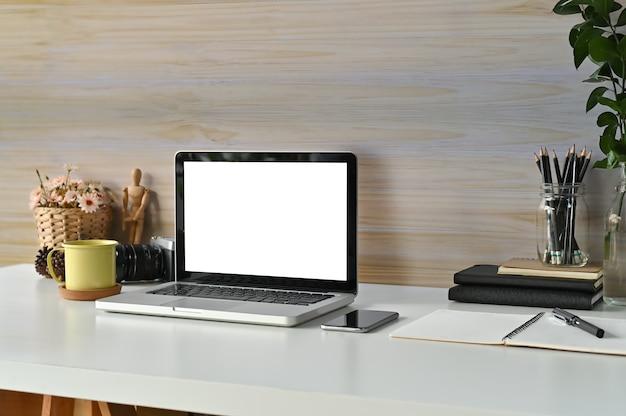 Workspace makieta laptop, kubek kawy, książki i materiały biurowe na biurku pracy.