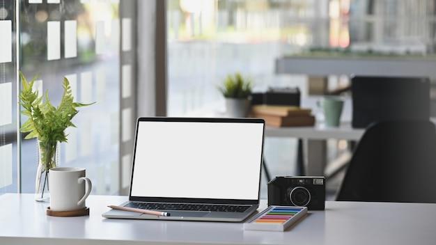 Workspace makieta laptopa na stole z kamerą, kawą i rośliną w nowoczesnym pokoju biurowym.