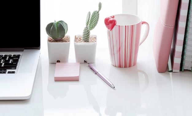 Workspace pojęcie z laptopem, kubkiem i książką na bielu stole, kopii przestrzeń.
