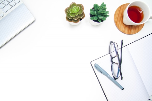 Workspace z laptopem, notatnikiem, sketchbook, sukulentem, filiżanką herbata na białym tle.