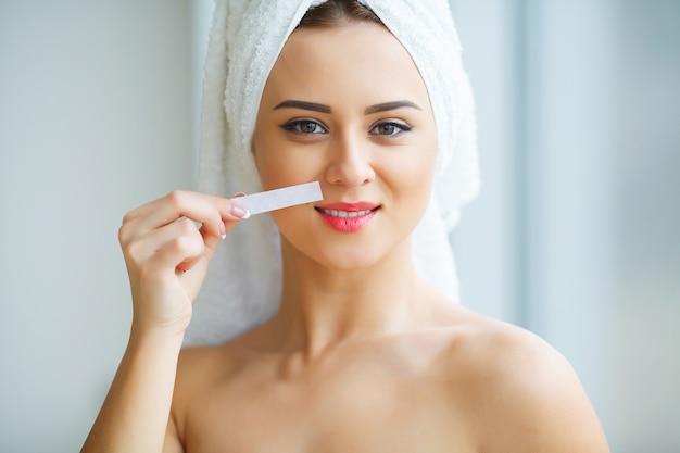Wosk do depilacji, młoda kobieta otrzymująca depilację twarzy