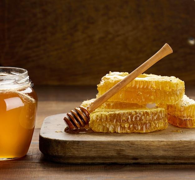 Wosk o strukturze plastra miodu z miodem na drewnianej desce i drewnianą łyżką, brązowy stół