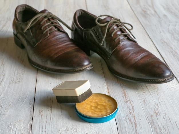 Wosk ochronny do obuwia skórzanego. koncepcja pielęgnacji obuwia. para klasycznych butów na drewnianej podłodze.
