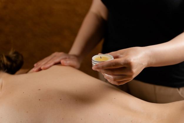 Woskowanie masażu ciała świecą. zabieg spa piękności. masaż tajski ciepłym woskiem.