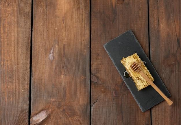 Woskowy plaster miodu z miodem na czarnej desce i drewnianą łyżką, brązowy stół, widok z góry