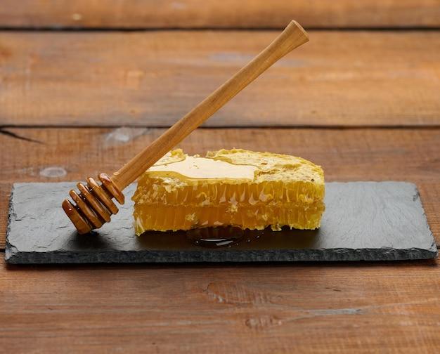 Woskowy plaster miodu z miodem na czarnej desce i drewnianą łyżką, brązowy stół