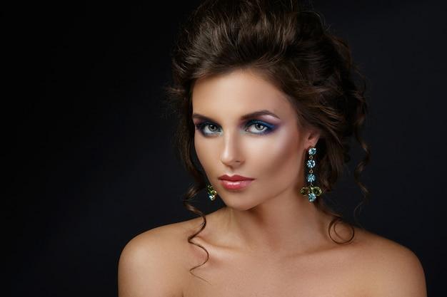 Woung kobieta ubrana w piękne kolczyki z kamieniami szlachetnymi