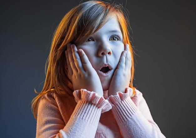 Wow atrakcyjna nastolatka półdługości portret przedni na ciemnym niebieskim tle studio