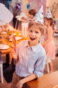 Wow emocje. miły dzieciak, utrzymujący uśmiech na twarzy podczas zabawy z przyjaciółmi