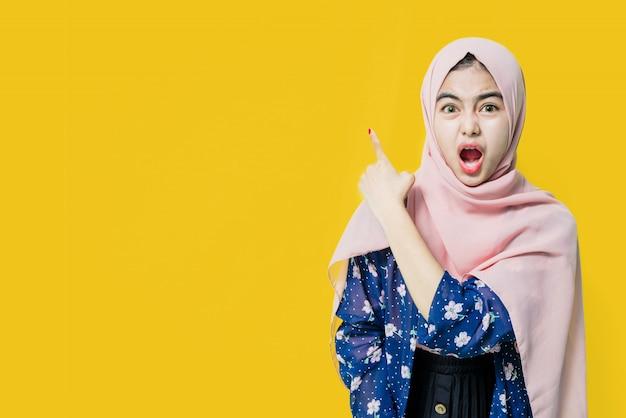 Wow i zaskoczona twarz azjatyckiej kobiety z ręką punkt na pustej przestrzeni