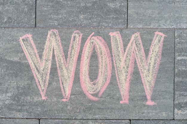 Wow napisane na szarym chodniku
