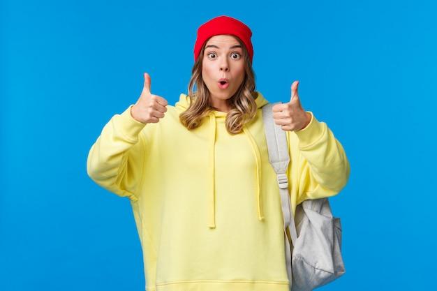 Wow, naprawdę fajna, dobra robota. imponująca, ładna blond młoda studentka w czerwonej czapce i żółtej bluzie z kapturem, nosząca plecak, chwal koleżankę dobrą robotę, pokaż kciuki w górę lub coś podobnego