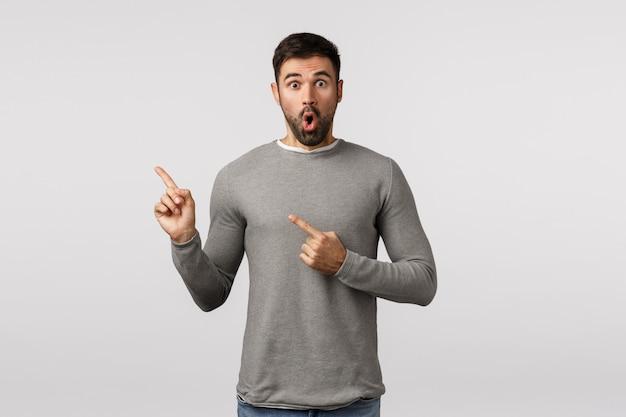 Wow, niesamowita niespodzianka, spójrz na to. zdziwiony i zdziwiony przystojny brodaty mężczyzna w szarym swetrze, z trudem łapiąc powietrze, gapi się pod wrażeniem, wskazując lewy górny róg, wskazując promocję,