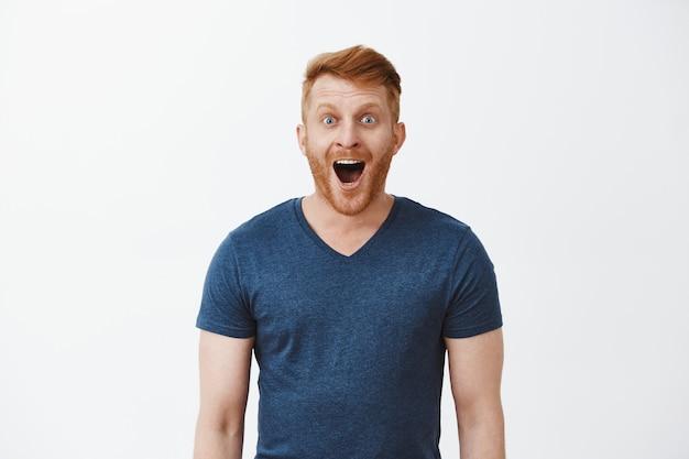 Wow, niesamowite. portret uroczego i podekscytowanego przystojnego, szczęśliwego rudowłosego mężczyzny z włosiem, opadającą szczęką i szeroko uśmiechniętego, wpatrującego się z podekscytowanym wyrazem na coś imponującego i ekscytującego
